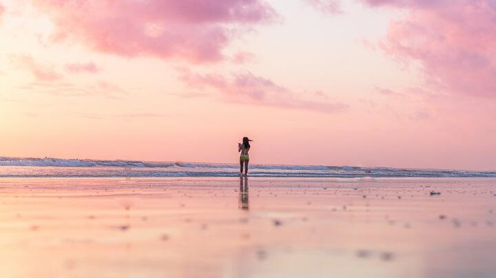 mujer-en-una-playa-de-arena-rosa